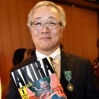 Manga artist Katsuhiro Otomo smiles Dec. 12 after receiving France's Order of Arts and Letters at the French Embassy in Tokyo. On Thursday he was honored for lifetime achievement at the Angouleme comics festival in France. | AFP-JIJI