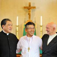 Former inmate Hiroshi Igarashi (center) shares a lighthearted moment with Rev. Hideo Kato (left) and friar Hernandez at a church in Tokyo. Igarashi spent 20 years in jail, and now runs an NPO that helps newly released prisoners. | KYODO