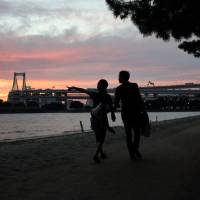 A couple walk in front of the Rainbow Bridge at dusk last August in Tokyo's Odaiba waterfront district. | BLOOMBERG
