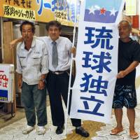 Chosuke Yara (center), leader of the Kariyushi Club, formerly called the Ryukyu Independence Party, and his supporters hold a banner calling for Okinawa's independence from Japan in Naha, Okinawa Prefecture, on Oct. 13. | KYODO
