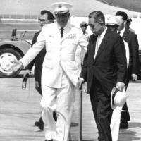 Prime Minister Eisaku Sato arrives at Naha airport in August 1965 and is met by Lt. Gen. Albert Watson, the islands' U.S. administrator. | KYODO