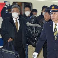 A suspect in recent shoplifting and food-tampering incidents is escorted by police at JR Shinagawa Station on Sunday. | KYODO