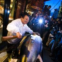 Kiyoshi Kimura removes the fin from the bluefin tuna that he paid ¥4.51 million for in the Tsukiji market's first auction of the year Monday. He posed for the cameras at his Sushi Zanmai restaurant near the market. | REUTERS