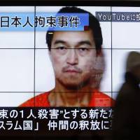 A man walks past screens displaying a television news program showing an image of Kenji Goto, one of two Japanese citizens taken captive by Islamic State militants, on a street in Tokyo on Sunday. | REUTERS