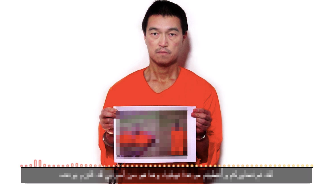 Screenshot from a video uploaded Saturday night in which it is claimed that Haruna Yukawa has been executed. The video is comprised a still image of hostage Kenji Goto holding a photo of the alleged killing  and the voiceover of a man who claims to be Goto.