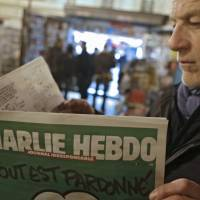 Cover story: A man reads the latest issue of Charlie Hebdo by a newsstand in Nice, southeastern France. The deadly terrorist attack on the office of the satirical magazine — and the publication's defiant response — have sparked debate in Japan as elsewhere about the limits of free speech. | AP