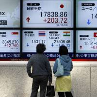 Watching the future: Pedestrians in Tokyo look at the stock market indices of various countries over the New Year's holiday.   REUTERS