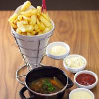 Saucy: The fries at Pommeke offers come with a selection of delicious sauces served to the side, and the order shown here comes with a Flemish carbonade. | COURTESY OF POMMEKE