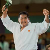 Moment in time: Judoka Hitoshi Saito celebrates his gold medal-winning triumph in the men's over-95 category at the 1984 Los Angeles Summer Olympics. Saito, who repeated as champion at the 1988 Seoul Games, died on Tuesday at age 54.   KYODO