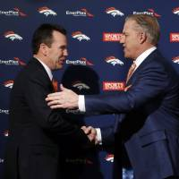 Together again: New Broncos head coach Gary Kubiak (left) is greeted by general manager John Elway in Englewood, Colorado, on Tuesday. | AP