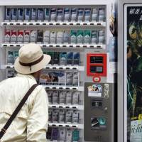 A pedestrian looks at a cigarette vending machine in Tokyo in April 2012. | BLOOMBERG
