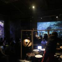 Surround sound: Musicians are scattered throughout the venue and two screens project images throughout a previous performance by the Kansai-based Enso Watt, who draw inspiration from Igor Stravinsky's 'The Rite of Spring.' | AITO KODAMA