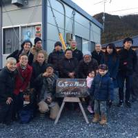 Broken but together: A photo outside Cafe De Monk in Minamisanriku's temporary-housing community after the 3/11 disaster. Mockett's son Ewan stands in front of various people in Mockett's book, 'Where the Dead Pause, and the Japanese say Goodbye.' Mockett herself is at the back on the far left, standing behind her mother.   MARIE MUTSUKI MOCKETT