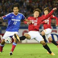 Back to the basics: Yuji Nakazawa (left) and Yokohama F. Marinos slumped to seventh place in the J. League in 2014 after finishing second the previous year.   KYODO