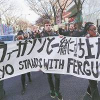 Up in arms: Members of the African American Youth Travel Program and others march in Shibuya on Dec. 6 in solidarity with protesters who have taken to the streets across the U.S. in the wake of the shooting of Michael Brown, an unarmed black man killed by police in Ferguson, Missouri, in August. | NAYALAN MOODLEY (DARC.JP)