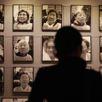 Inconvenient details: A visitor looks at portraits of late former 'comfort women' at the House of Sharing, a nursing home for wartime sex slaves in Gwangju, South Korea. There are only a few dozen women left who are registered with the South Korean government as former sex slaves of the Japanese military — down from a peak of more than 230. Their average age is 89. | AP