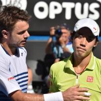 Thousand-yard stare: Stan Wawrinka (left) consoles Kei Nishikori after winning their Australian Open quarterfinal in straight sets on Wednesday. | AFP-JIJI