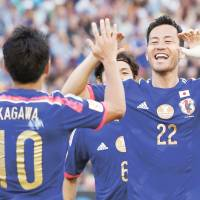 Nothing too tough: Japan's Maya Yoshida celebrates with Shinji Kagawa after scoring against Palestine during their Group D match at the Asian Cup on Monday in Newcastle, Australia. Japan won 4-0. | REUTERS