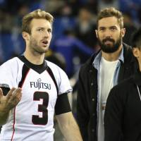 Oh brother: Fujitsu quarterback Colby Cameron (left) and older brother Jordan, a tight end with the Cleveland Browns, chat on the sidelines after Fujitsu's 33-24 win over Kwansei Gakuin University in the Rice Bowl at Tokyo Dome on Saturday.   KAZ NAGATSUKA