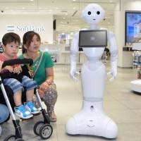 Unveiled in June, 2014, 'Pepper,' a humanoid robot that can communicate with people and sense emotions, made its debut as a clerk at a SoftBank Corp. mobile phone store in July. SoftBank has further developed an application, which can help prevent dementia through conversations and ask questions to perform a simple diagnosis of symptoms. | KYODO