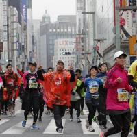 Participants run through the Ginza shopping district during the 2015 Tokyo Marathon on Sunday. | AP