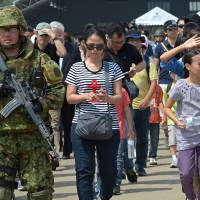 Japanese soldiers escort people Sunday during a Non-Combatant Evacuation/Transportation of Japanese Nationals Overseas exercise as part of the annual combined military exercises coined Cobra Gold 2015 at a military base in Sattahip.  | AFP-JIJI