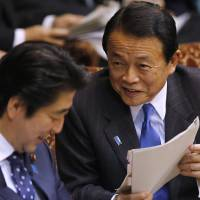 Deputy Prime Minister and Finance Minister Taro Aso speaks to Prime Minister Shinzo Abe during an Upper House committee session at the Diet in Tokyo on Feb. 3. | REUTERS