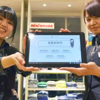 Sales staff at the Mitsukoshi Ginza Store are inviting Mandarin speakers to indicate what they want with the aid of these tablet computers. Department stores are boosting services for Chinese visitors. | KYODO
