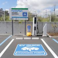 A quick charger is pictured outside a FamilyMart convenience store in Tokyo last April. Nissan Motor Co. says there are now more car charging points in Japan than gas stations. | KYODO