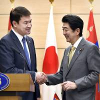 Prime Minister Shinzo Abe and Mongolian Prime Minister shake hands Tuesday at the prime minister's office in Tokyo following a news conference in which they announced the signing of a bilateral economic partnership. | KYODO