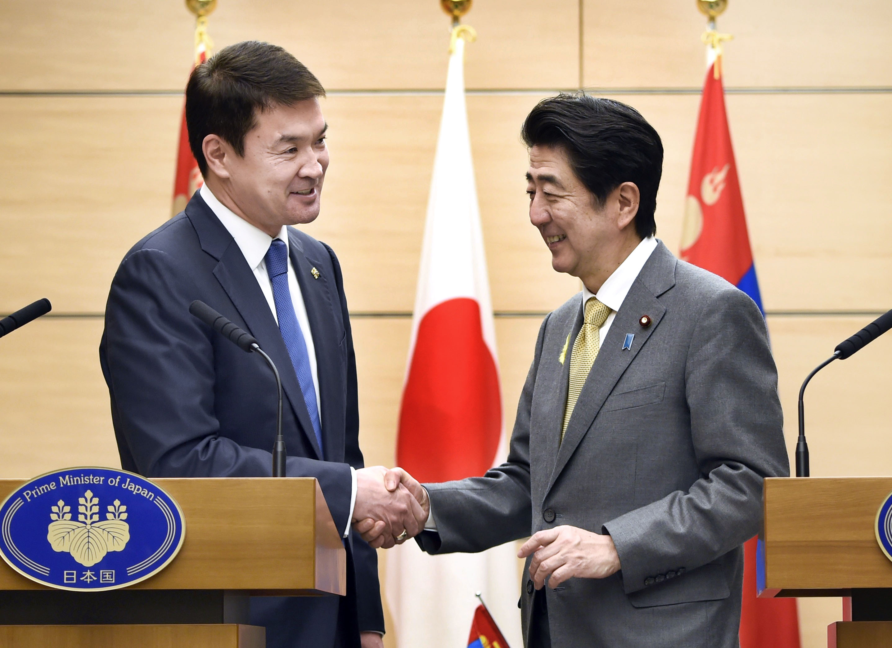 Prime Minister Shinzo Abe and Mongolian Prime Minister shake hands Tuesday at the prime minister's office in Tokyo following a news conference in which they announced the signing of a bilateral economic partnership.   KYODO