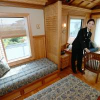 A Kyushu Railway Co. attendant shows off a deluxe suite aboard the luxury Seven Stars train in this image from 2013. The government said Friday it would fully privatize JR Kyushu in fiscal 2016, as its businesses are in good health. | KYODO