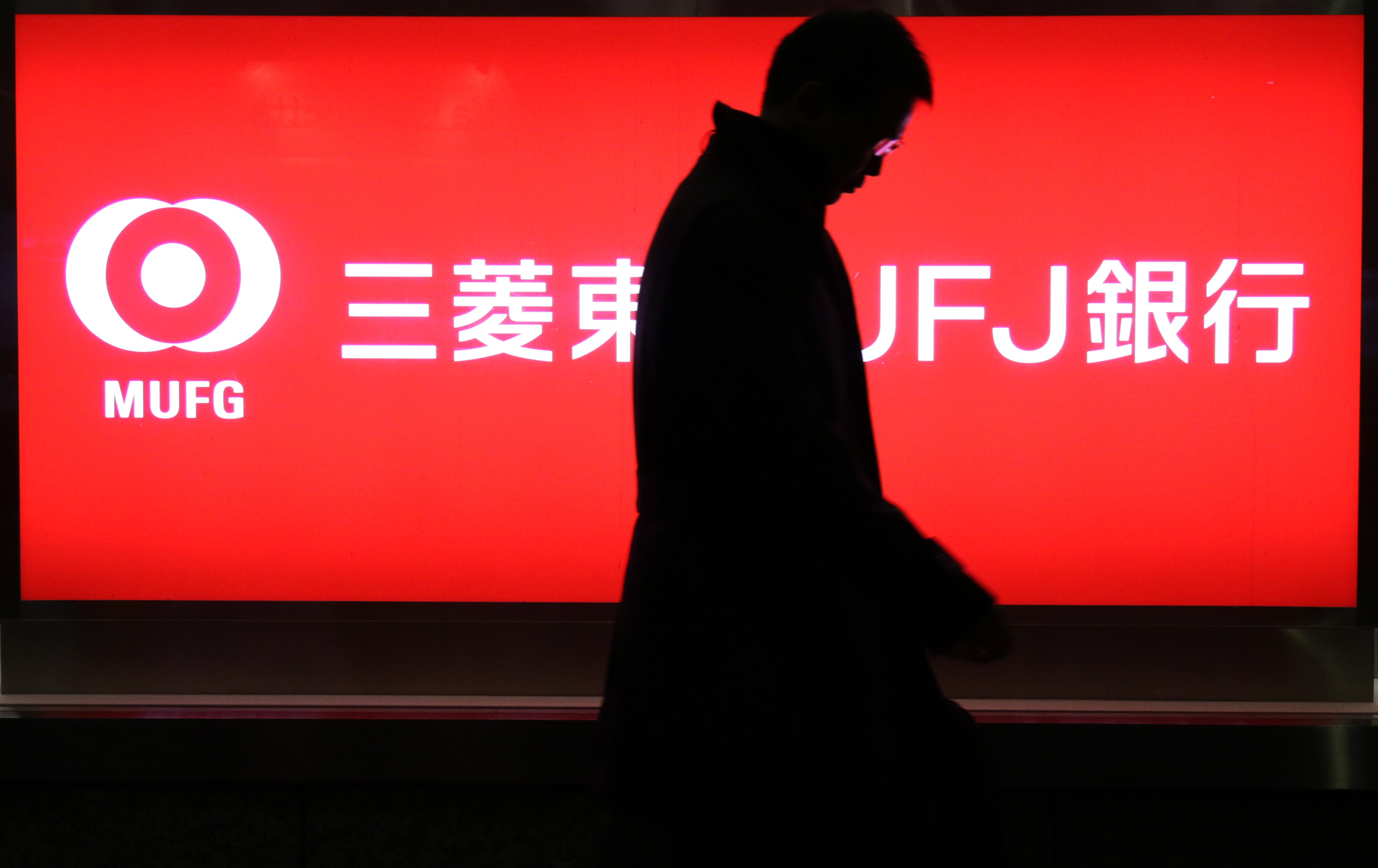 A customer walks past a Bank of Tokyo Mitsubishi UFJ Ltd. branch in Tokyo on Feb. 2. As Japan's sovereign bond yields languish near zero, the regular payouts to megabank shareholders are starting to look more attractive to investors. | BLOOMBERG