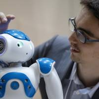 Sebastien Cagnon, behavior architect at Aldebaran Robotics SA (right), holds a demonstration with the firm's NAO robot at the International Robot Exhibition 2013 in Tokyo in November 2013. Mitsubishi UFJ Financial Group Inc. will trial the device in two branches in Tokyo. | BLOOMBERG