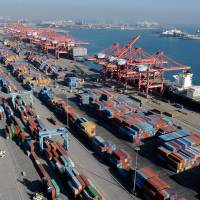 Containers and ships sit idle at the Port of Long Beach, California, on Friday. Vessel loading and unloading operations are set to resume Monday at U.S. West Coast ports, after they were suspended over the weekend amid strike actions by thousands of port workers. | REUTERS
