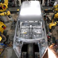 Robots weld the body of a vehicle at Nissan's plant in Kanda, Fukuoka Prefecture. According to new research, lower costs of industrial robots may see factories use them more frequently to replace salaried workers. | BLOOMBERG