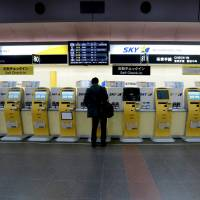 A traveler uses a Skymark Airlines Inc. automated check-in machine at Haneda Airport in Tokyo on Jan. 29.   BLOOMBERG