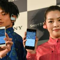 Models show off Sony's new Smart B-Trainer SSE-BTR1, a wearable gadget for runners, at a press conference in Tokyo on Thursday. The device combines a music player with six sensors that monitor metrics like heart rate and running pace. | AFP-JIJI