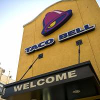 The Taco Bell Corp. logo is displayed on the facade of a restaurant in San Francisco in 2013. The major U.S. fast food chain will reopen restaurants in Japan, with the first outlet expected to open in central Tokyo by this fall. | BLOOMBERG