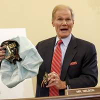 U.S. Senate Commerce Committee member Sen. Bill Nelson displays parts of a defective air bag made by Takata Corp., which has been linked to multiple deaths and injuries in accidents in the U.S., during a hearing in Washington in November. | AP