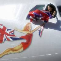 A flight attendant on Virgin Atlantic Airways' last flight between Narita and Heathrow airports waves a Union Jack from the cockpit as it leaves Japan on Sunday. The British airline has halted Narita-London flights as it revises its international routes. | KYODO