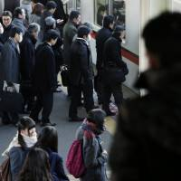 Commuters wait for a train in Inzai, Chiba Prefecture, in December. Real wages fell 1.4 percent that month, according to data from the labor ministry. | BLOOMBERG
