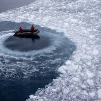 Chilean Navy officers push away ice by moving their boat in circles as they approach the Aquiles navy ship where they were to pick up international scientists and take them to Chile's Bernardo O'Higgins scientific station in Antarctica on Jan. 22. | AP