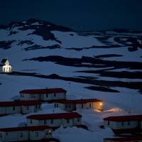 A church is lit in the town of Villa Las Estrellas on King George Island, Antarctica, on Jan. 20. Geologists are entranced by Antarctica's secrets. Clues to answering humanity's most basic questions are locked in this continental freezer the size of the United States and half of Canada: Where did we come from? Are we alone in the universe? What's the fate of our warming planet? | AP