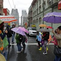 Pedestrians take cover from rain in the Chinatown district of San Francisco on Friday. | AP