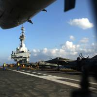 French aircraft sit on the flight deck of the French Navy aircraft carrier Charles de Gaulle operating in the Persian Gulf on Monday. | AFP-JIJI