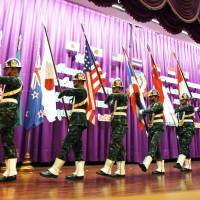 Thai soldiers carry national flags at the opening ceremony for Cobra Gold at a military academy in Nakhon Nayok province on Monday. The drills are scaled back this year. | REUTERS