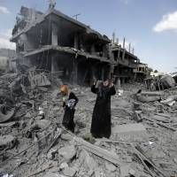 A Palestinian woman pauses amid destroyed buildings in the northern district of Beit Hanun in the Gaza Strip during a humanitarian truce on July 26, 2014. | AFP-JIJI