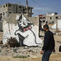 Palestinians walk past a mural of a kitten, presumably painted by the British street artist Banksy, on the remains of a house that witnesses said was destroyed by Israeli shelling last summer in the northern Gaza Strip town of Biet Hanoun, on Thursday.   REUTERS