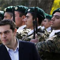 Greek Prime Minister Alexis Tsipras reviews an honor guard at the Presidential Palace during a welcoming ceremony ahead of a meeting with Cypriot President Nicos Anastasiades in Nicosia on Monday. | AP